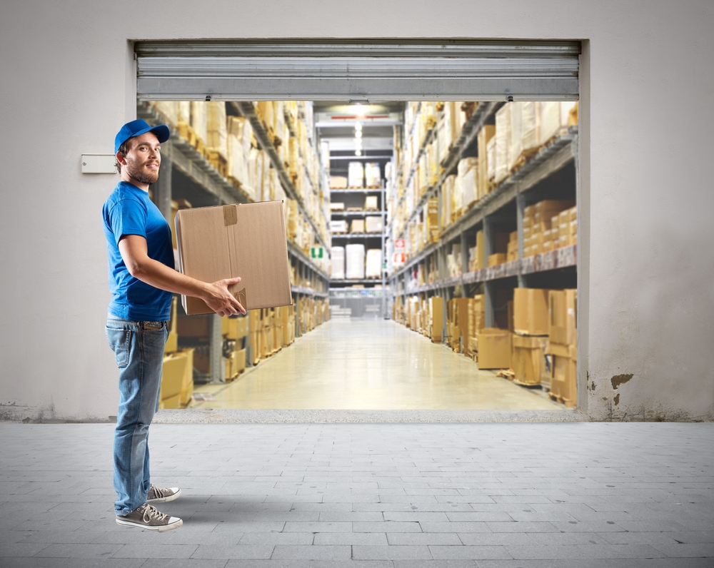 Supply chain - a man holding a box in a warehouse